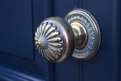 Close up gold metal door knob on a blue exterior house door.