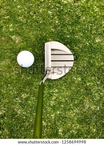 Close up golf mallet putter behind white golf ball