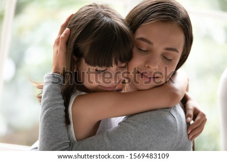 Close up gorgeous sisters different age hugging closed eyes enjoy moment of tenderness feels happy, mother and little daughter cuddling having strong bonds, adopted kid new mom reunification concept