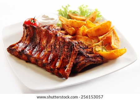 Close up Gourmet Grilled Pork Rib and Fried Potato Wedges on White Plate with Sauce and Veggies, Isolated on White Background.
