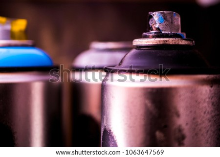 close up graffiti aerosol spray paint cans black background