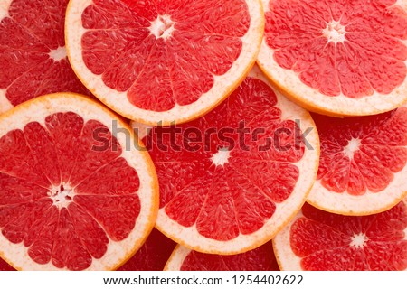 Close-up Grapefruit slices abstract background in Living Coral color of the Year 2019. Bright summer texture. #1254402622