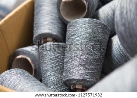 Close up gray silver yarn threads spools bobbin tubes