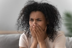 Close up grieving african woman sit on sofa covers mouth with hands crying suffers from loss or death of loved one, need help of grief counselling psychotherapy for cope with emotional problem concept