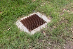 Close up Grille drain of sewer around the Grass field . Water recirculation system. Wastewater treatment.