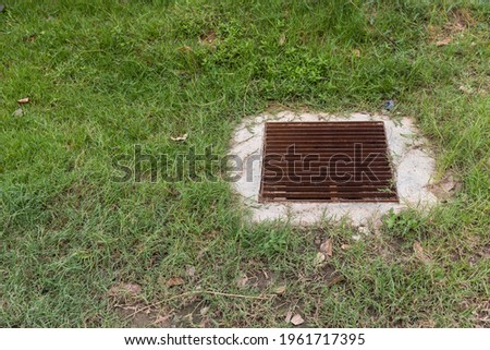 Close up Grille drain of sewer around the Grass field . Water recirculation system. Wastewater treatment. stock photo