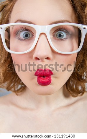 Close-up grimace of a funny woman with closed mouth