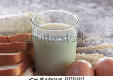 close up group of Nutrition Breakfast, like Breads, Corn, Milk, eggs on blurred wooden background. #1384602206