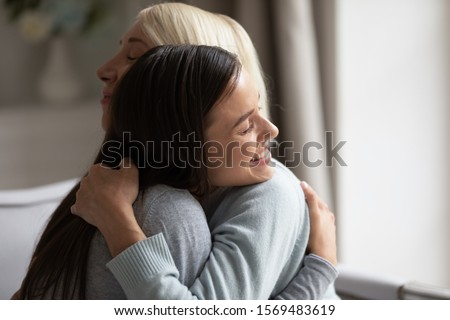 Close up grown up 20s daughter hugging elderly mother, multi-generational family feeling love and giving support, women closed eyes cuddling showing care, parent and children is our life value concept
