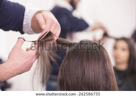 Close-up hairdresser cutting hair a woman in hairdresser salon.