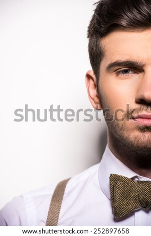 Close-up half face of young man with suspenders and bow-tie.