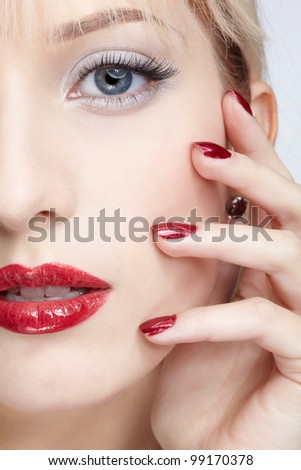 close-up half face portrait of beautiful woman with bright red lipstick and manicure
