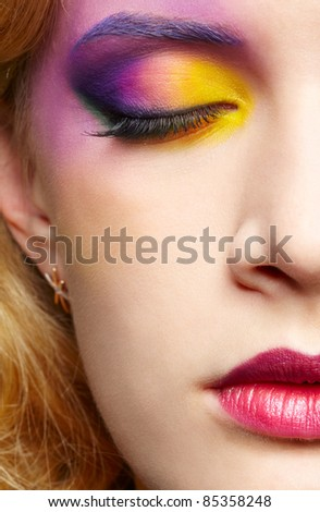 close up half face portrait of beautiful woman with colorful make-up with eyes shut