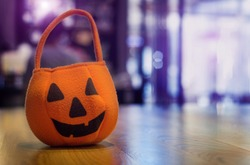 close up halloween bag on wood table and copy space with copy space on purple light on background