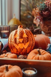Close up Halloween cozy mood composition on the windowsill. Lighting jack-o-lantern, decorative pumpkins, cones, candles on wooden tray near window. Hygge halloween home decor. Selective focus.