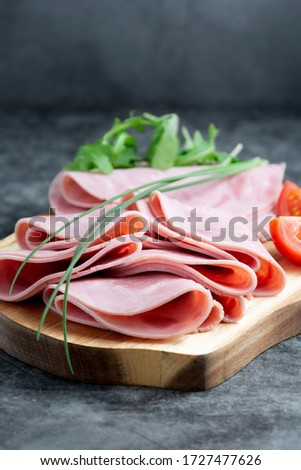 Close up ham slices isolated on cutting board over dark background. Photo stock ©