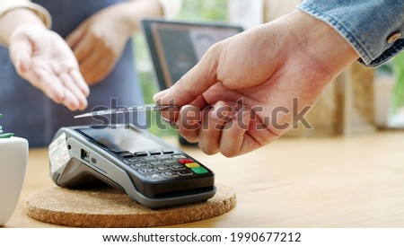 Close-up hand asia woman people work in small sme coffee cafe shop store owner use cashless wifi paywave nfc scan app smart pos reader sale in take out food drink order in urban city life contactless.
