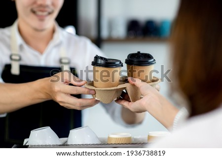 Close up hand. Asian young man or bartender serving paper coffee glass customer at coffee shop. making coffee in cafe. Concept sale paper bag and coffee. maker machine with portafilter