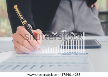 Close up hand businessman writing with pen, financial data and sales rates and market exchanges or appropriate paper reports with graphs showing business growth. Concepts of financial investment Stockfoto ©