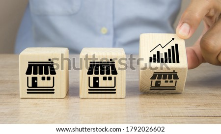 Close-up hand choose graph icon on cube wooden toy blocks place in line up with franchise business store icon. for small business growth and  branch expansion strategy of financial marketing planning. Stockfoto ©