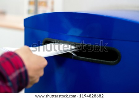 close up hand drop letter and documents in the blue postbox in post office mail #1194828682