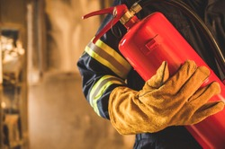 Close up hand Fireman,Firefighter holding the fire extinguisher.