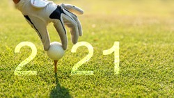 Close up hand Golfer woman putting golf ball for Happy New Year 2021 on the green golf for new healthy.  copy space. Healthy and Holiday Concept.