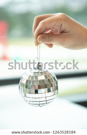 Close up hand held silver disco ball ready to decorate the venue