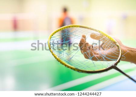 Close up hand hold broken strings of badminton racket