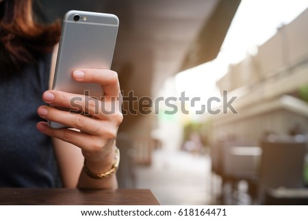 close up hand hold mobile cell phone device:focus on girl text on smart phone concept or teen people type digital content or teenager answer chat friends.