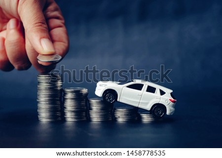 close up hand holding coin, stack of money and toy car on table, saving for future, manage to success transport business technology concept