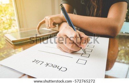 close- up hand holding pen on check list paper with tablet in vintage style #572765272