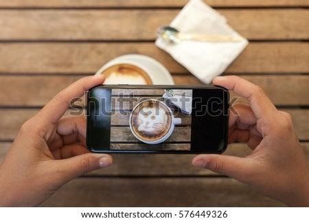 close-up hand holding phone taking coffee photo on table
