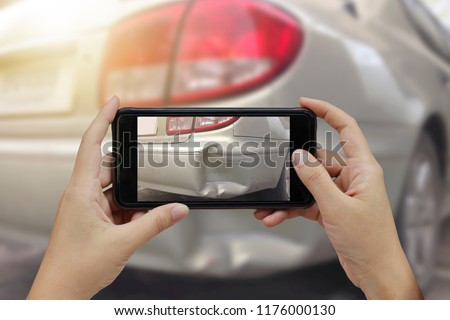 Close up hand holding smartphone and take photo at The scene of a car crash and accident, car accident for car insuranc claim.