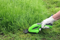 Close-up hand holds an electric manual grass trimmer and trims the border of vegetation. Copy space on green background