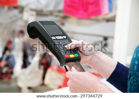 Close-up  hand holds  terminal and credit card in store