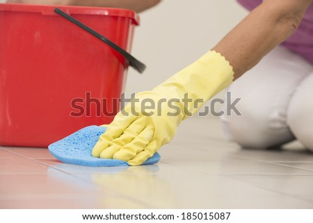 Close up Hand in yellow rubber glove cleaning floor tiles with sponge, with woman, housewife in blurred background and copy space.