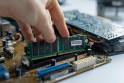 close up hand insert or install the ram memory component in the pc motherboard