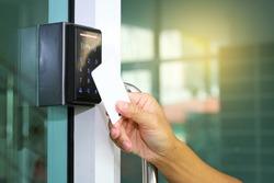 Close-up hand inserting keycard to lock and unlock door - Door access control keypad with keycard reader