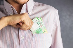 Close up hand of a man in a striped shirt holding 200 roubles banknote into pocket. businessman pulls money out of his breast pocket. Russian Ruble currency