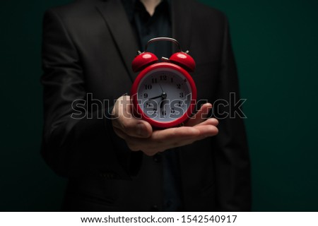Close-up hand of an unidentified young man in a dark shirt and jacket holds a red clock. The concept of lack of time or free time. Advertising concept