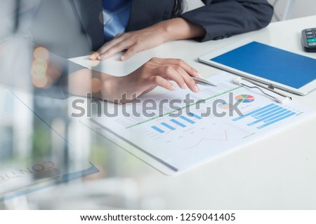 Close UP HAND of BUSINESS Woman Hold PEN and SPREADSHEET Graph Papers on Table. AUDIT TAX Return on Investment Analysis Shareholders and Capital MARKET. AUDITOR and Analytics Concepts