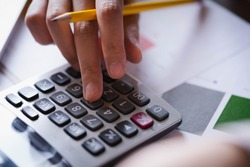 Close up hand of businesswoman or accountant working on calculator to calculate business data, and accountancy document. Business financial and accounting concept.