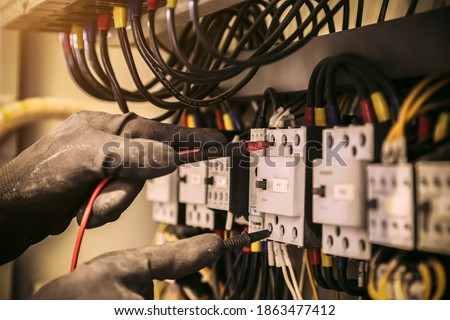 Close-up hand of electrical engineer using measuring equipment to checking electric current voltage at circuit breaker and cable wiring system for maintenance in main power distribution board. Stockfoto ©