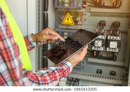 Close up hand of engineer or electrician man working check the electrical system with tablet at factory.  Stockfoto ©