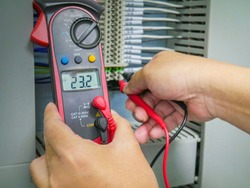 Close up hand of engineer to use digital clip ampere meter clamp to power cable for check Power current