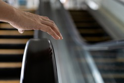 Close up,Hand of female with handrail of escalator,avoiding or not touching the handrail while using the escalator,dirt and accumulation of a pathogens,bacteria,virus that can cause contagious disease