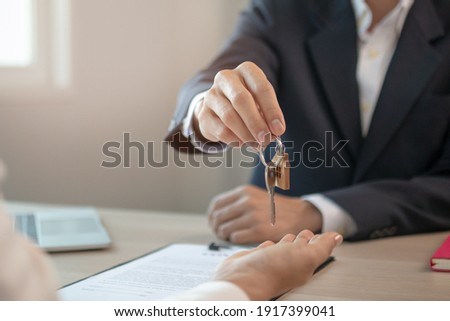 Close up hand of home,apartment agent or realtor was holding the key to the new landlord,tenant or rental.After the banker has approved and signed the purchase agreement successfully.Property concept. Foto stock ©