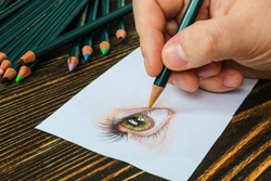 Close-up hand of illustrator drawing realistic eye on paper with pencils.
