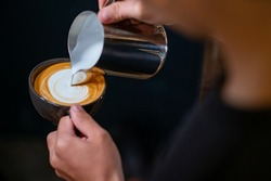 Close up hand of man barista pouring froth milk in espresso coffee in coffee cup making caffe latte art serve to customer. Small business cafe and restaurant owner and part time job working concept
